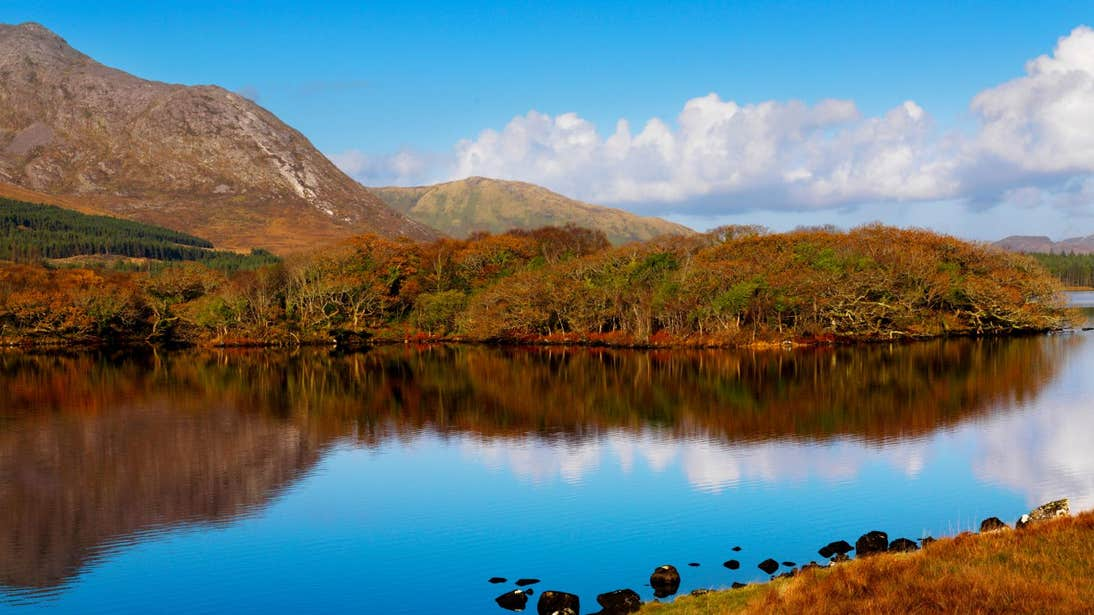 Golden hills reflecting on calm water at Lough Inagh, Galway