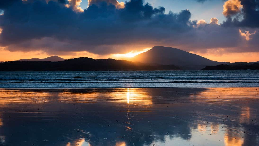 A stunning sunset behind mountains at Downings Beach.