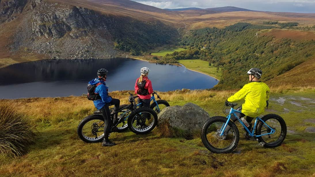 Three people on bikes looking at gorgeous views of the Wicklow Mountains