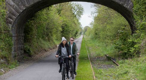 A couple cycling  under a bridge on The Old Rail Trail in County Westmeath