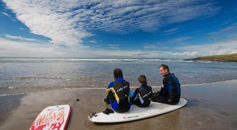 Family at the beach in West Cork with surfboards