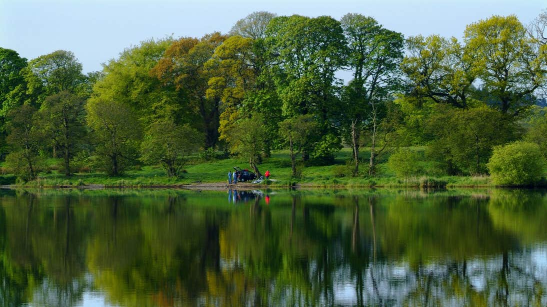 Image of Lough Muckno, Monaghan, surrounded by trees with people in the distance